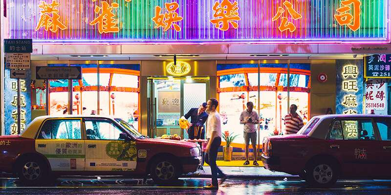 Adam Charlton walking past taxis in the streets of Hong Kong