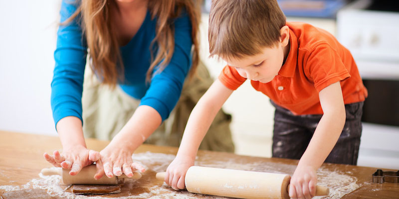Young child using a rolling pin while baking with mum