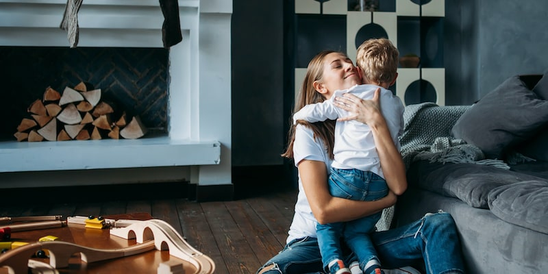Mother hugging her child in living room of home