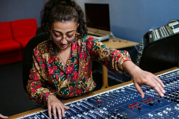 Female student using sound mixer in sound recording studio