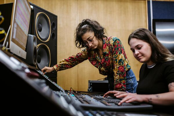 Two female students using sound mixing desk in sound recording studio
