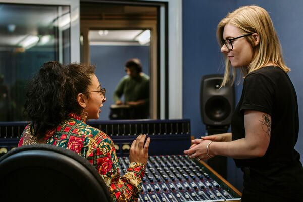 Two female students speaking in front of sound mixing desk
