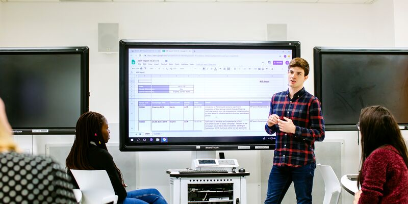 A male student presenting to a group of people
