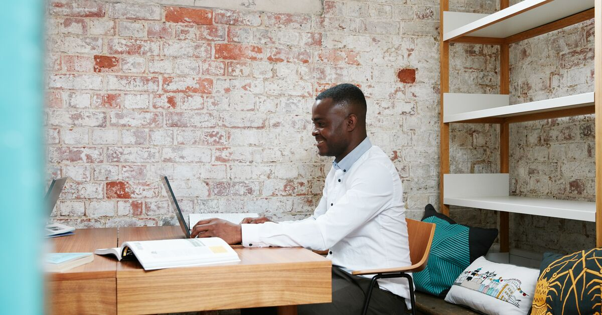 Man sits in office space and smiles while using laptop