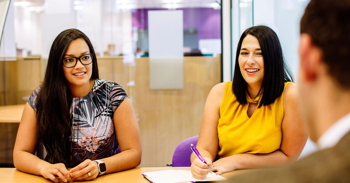 Two women laugh and smile in professional services meeting