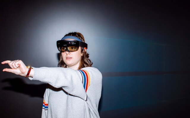 A young woman wearing an augmented reality headset manipulates a virtual object