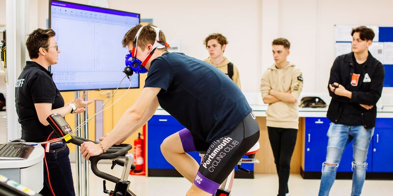 Male student training on stationary bike in front of class