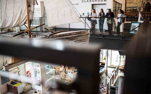 Female students in museum looking at antique boat