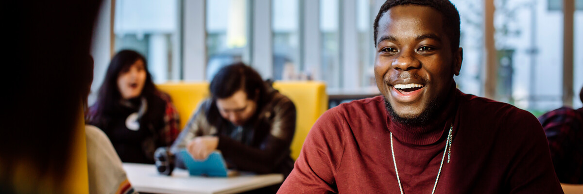 Male student in red jumper smiling in library