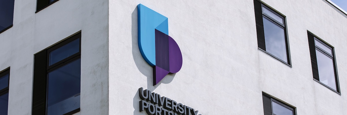 University of Portsmouth logo on white brick building