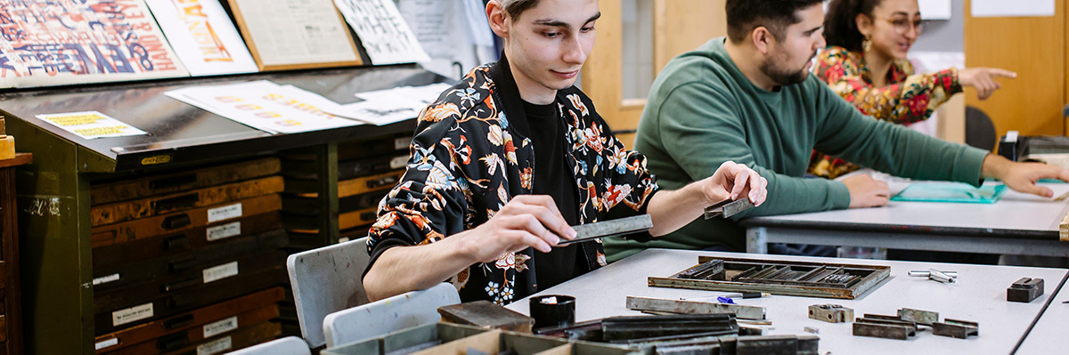 Three students working in the letterpress facility