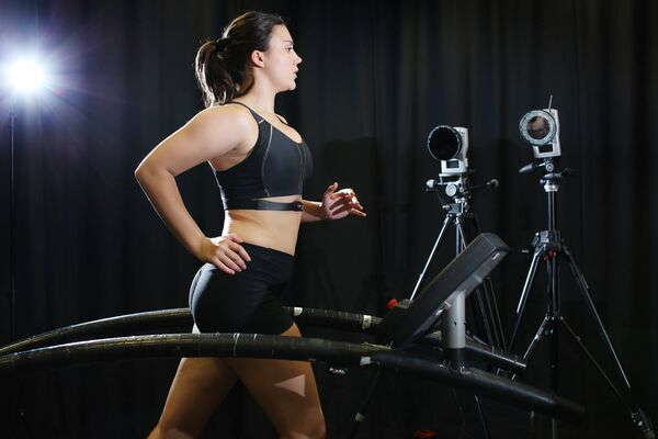 Woman running next to cameras in bra testing facility