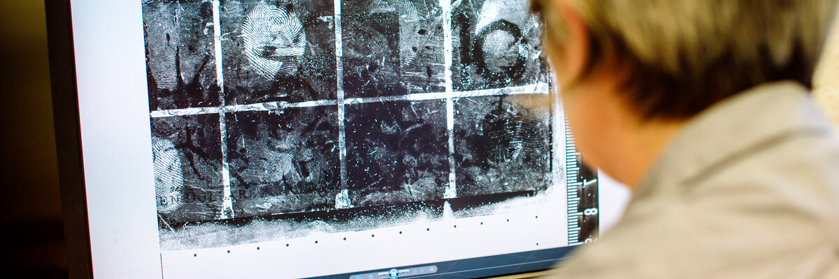 a man looking at photos of fingerprints on a PC monitor