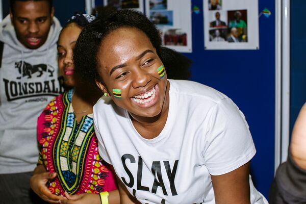 Female student smiling, she has Tanzanian flags painted on her cheeks