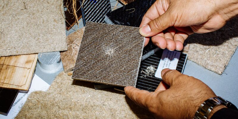 male hands hold small solid square panel which is made from materials including plant waste