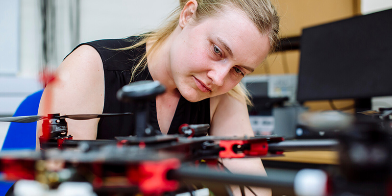 Female engineering student examining robot