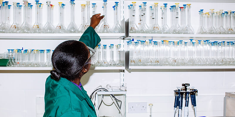 Biotechnology student reaches for laboratory glassware
