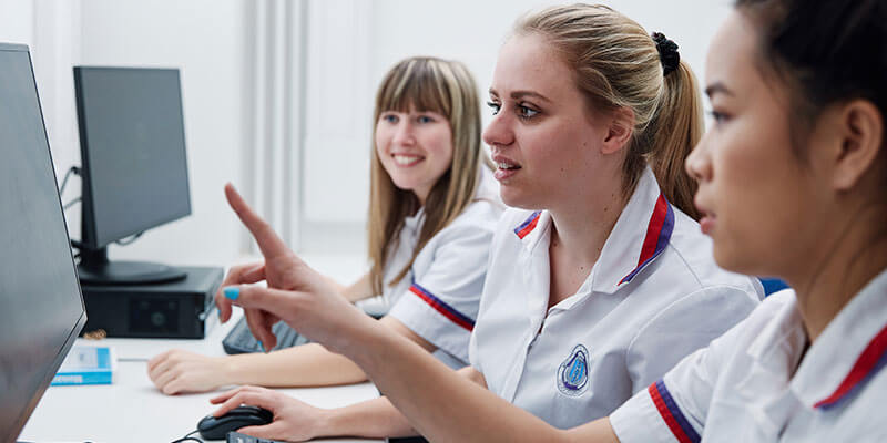 Student nurses collaborating around a computer