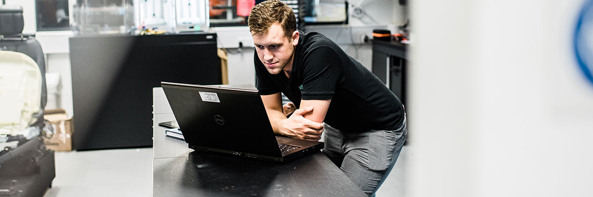 Engineering and management student uses laptop at work