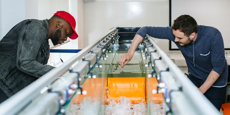 Two students conduct an experiment using a wave making water flume