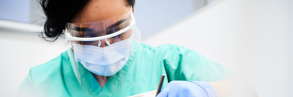 dental hygiene and dental therapy student examines patient teeth