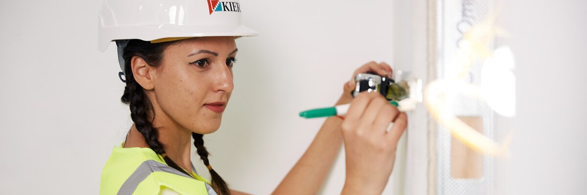 Young woman wearing protective hat and measuring wall
