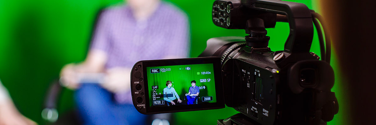 Journalism with Media student uses green screen reporting room