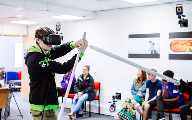 Student wearing VR headset using motion capture sword