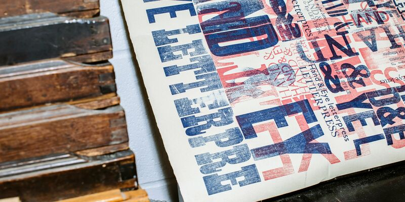 A page of typography and lettering next to a letterpress