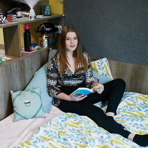 Female student relaxed at home with book