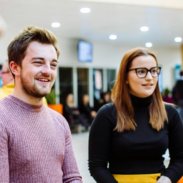 Male and female University of Portsmouth students talking and smiling
