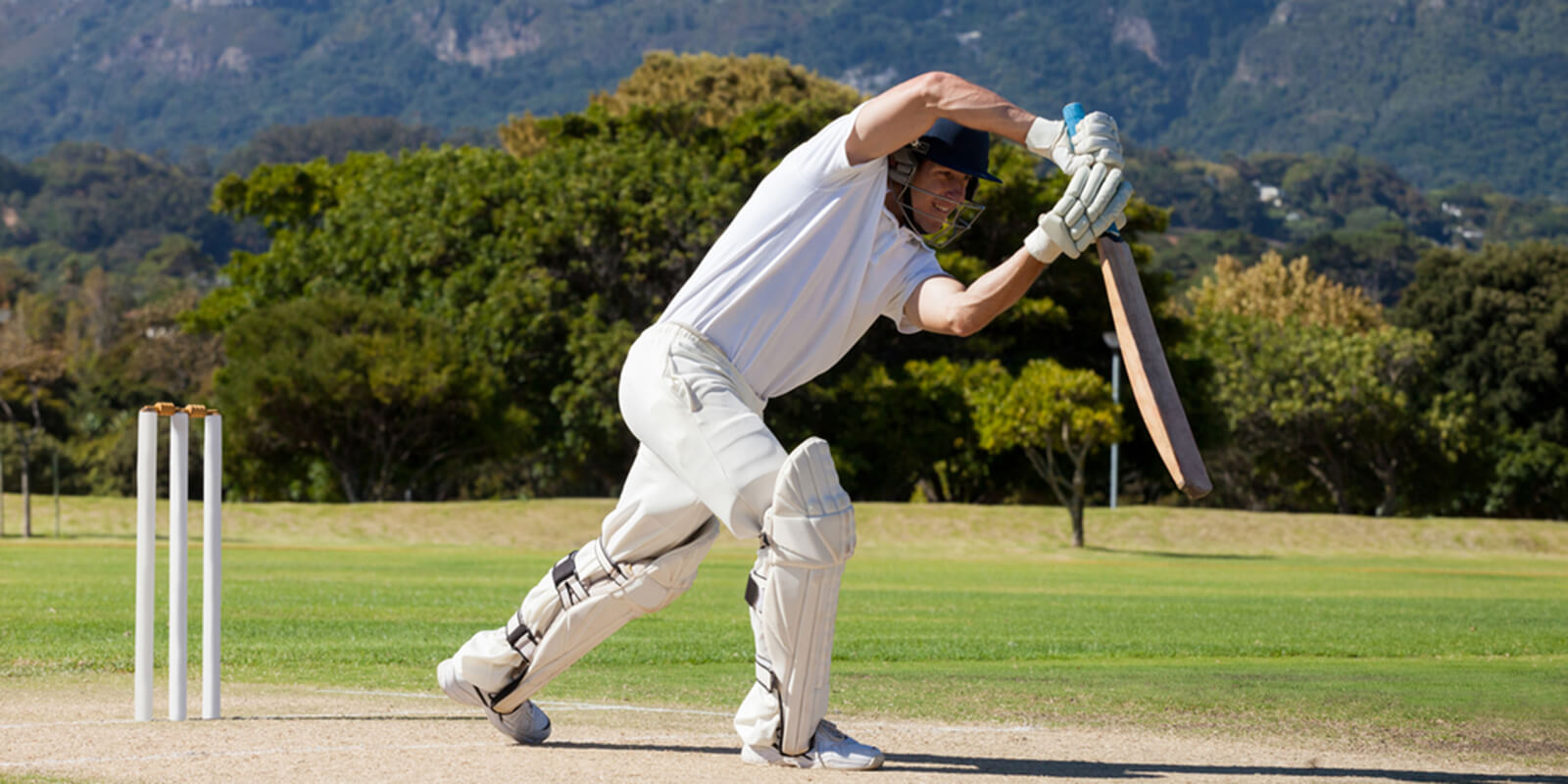Cricketer batting a ball in front of a wicket on a sunny day