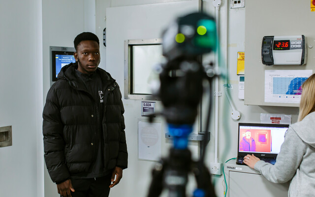 A student looks into a camera
