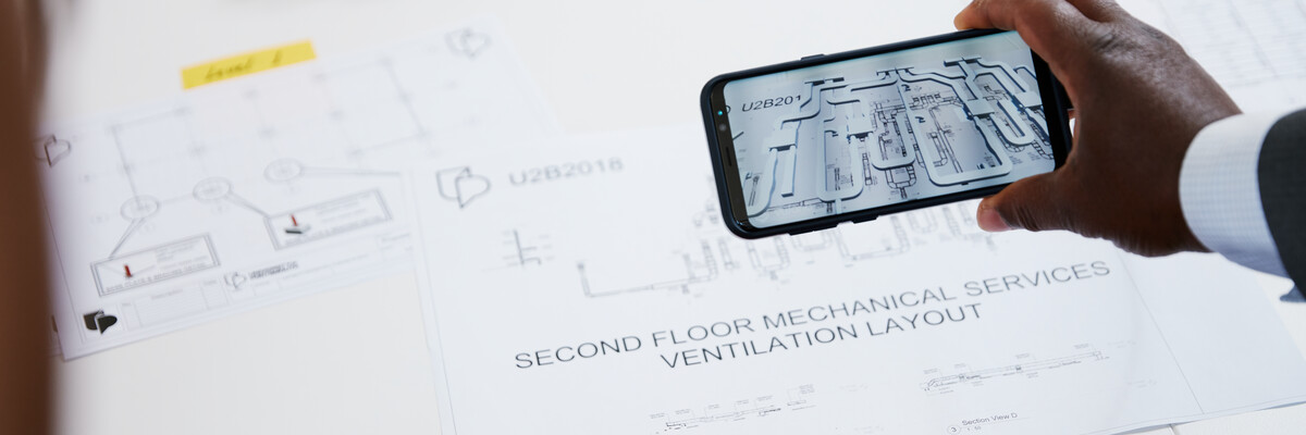 Hand-held mobile device displays augmented reality image of building plan