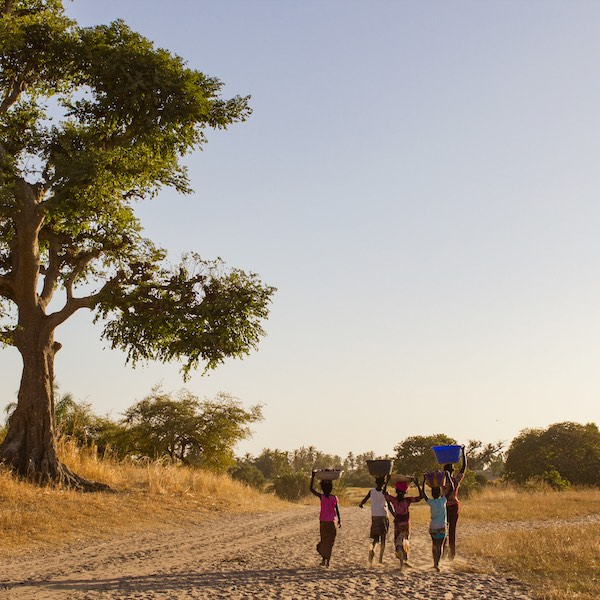 Children walking in arid African landscape