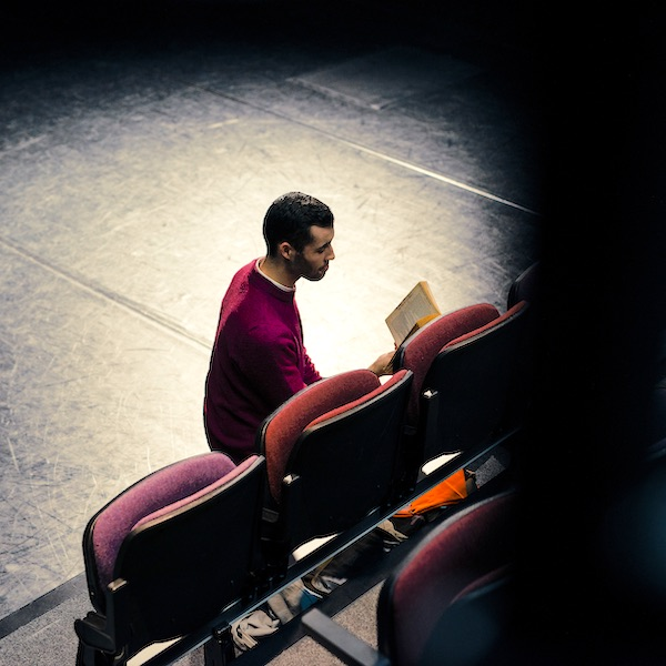 Man reading a play in dimly-lit theatre space