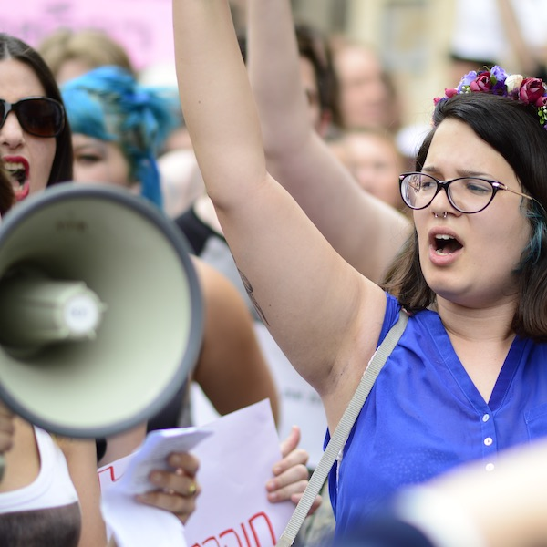 Female protester raising her arms during a march