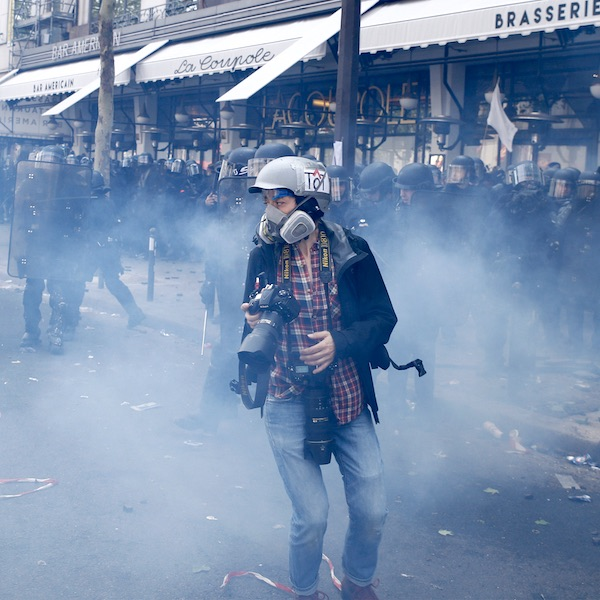 Photojournalist surrounded by riot police, Paris, France