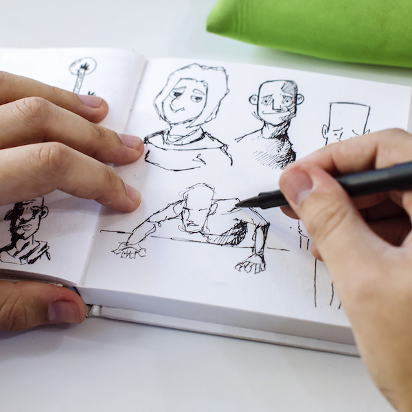 Illustrator drawing in sketch book, close-up