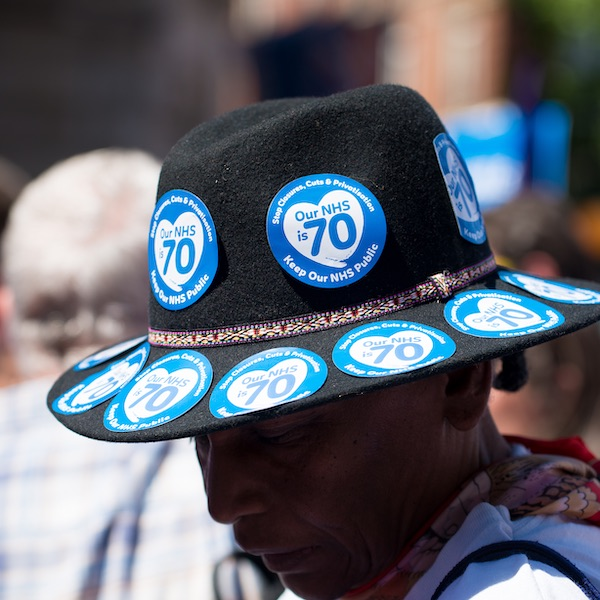 Man wearing a hat with pro-NHS advertising stickers
