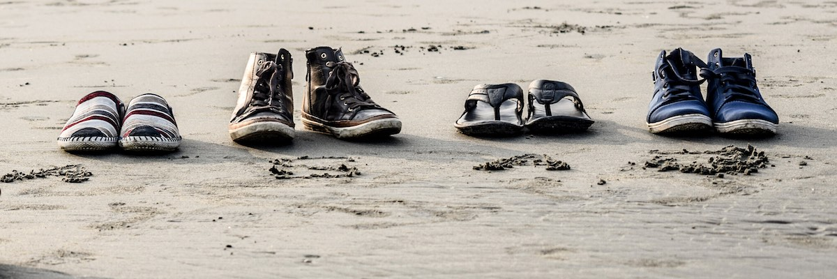 Empty pairs of shoes left on the beach