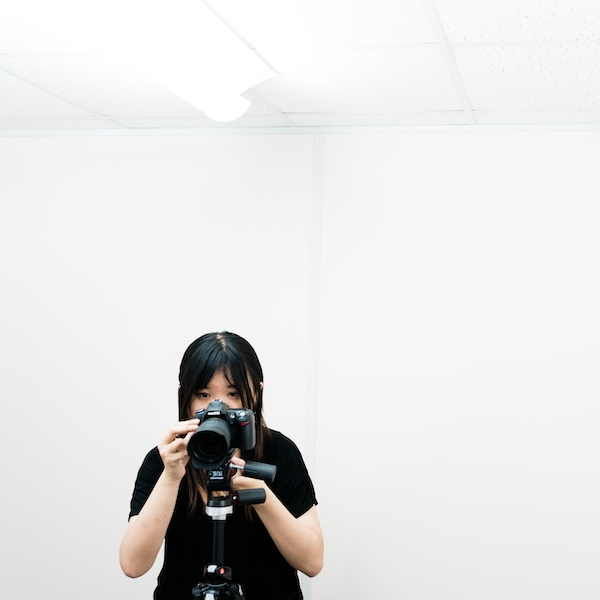 Female photographer taking pictures in white room