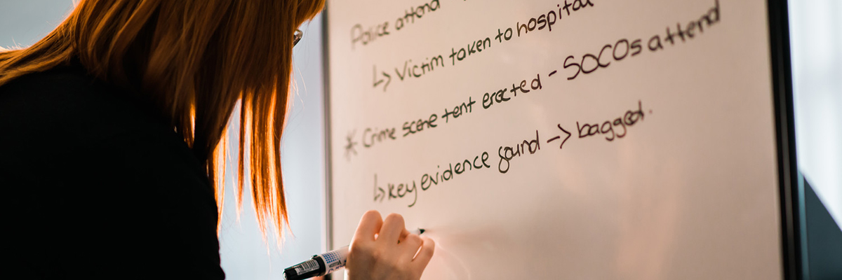 Woman writing forensic studies notes on whiteboard
