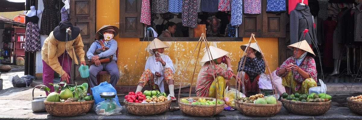 Asian women sitting on the floor at a market