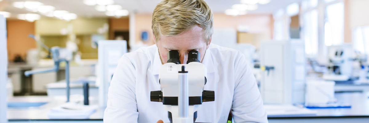 Male scientist using a microscope in laboratory