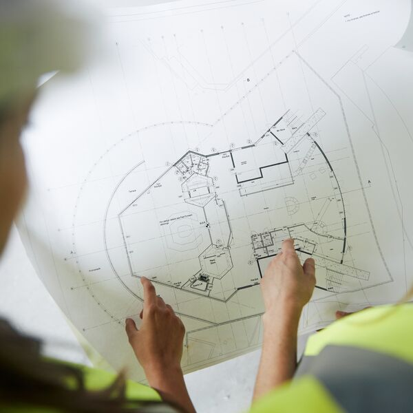 Civil engineers look at blueprints for a building