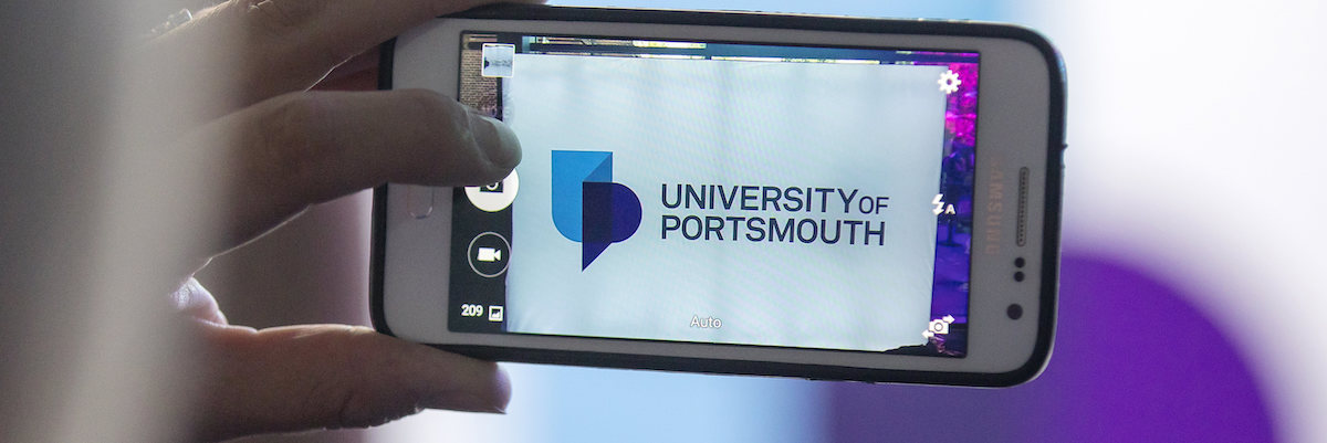 person using phone to take picture of UoP branding
