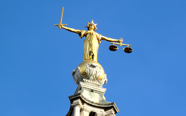 Law statue against blue sky