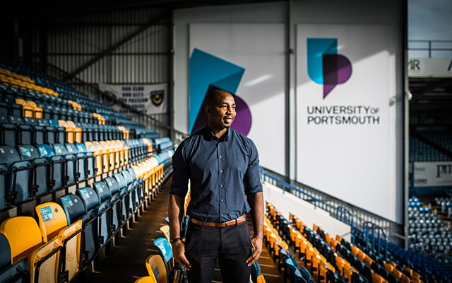 BAME male standing in colourful stadium seats