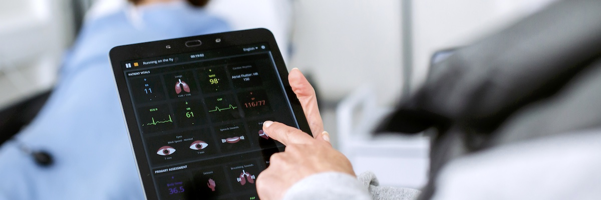 Doctor checking patient's vital signs on iPad